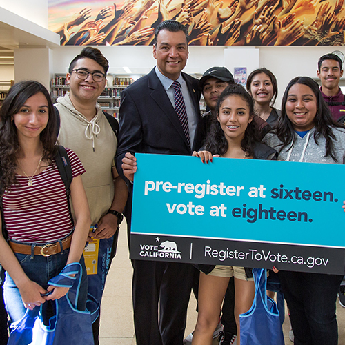 Photo of Secretary of State Alex Padilla with a group of students holding a sign that read pre-register at sixteen. vote at eighteen